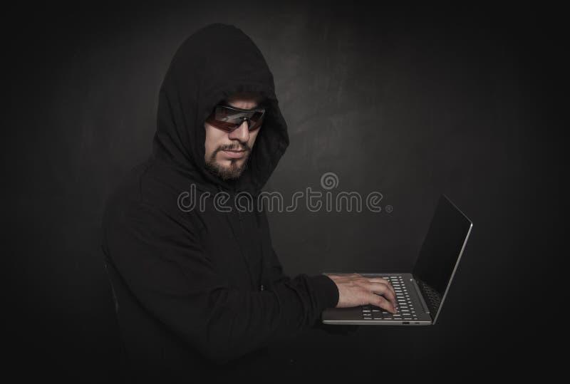 Man hacker programmer using laptop on dark royalty free stock images