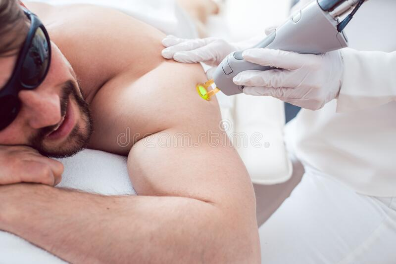 Man in a hair removal studio. Man under treatment in a hair removal studio stock image