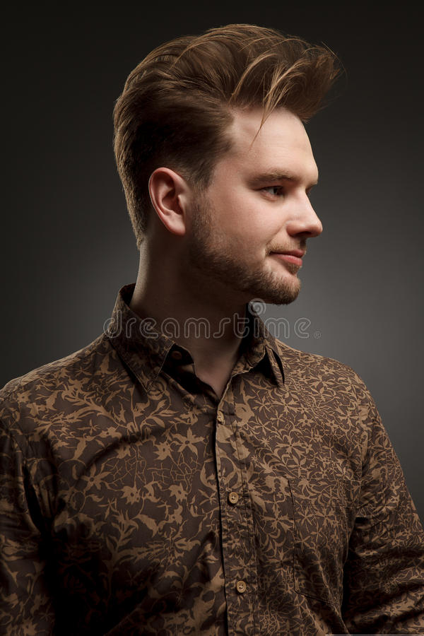 MAN haircut. Stylish young man with trendy hairstyle pose in studio. In shirt with pattern. Vogue. Copy-space. MAN haircut. Stylish young man with trendy stock photo