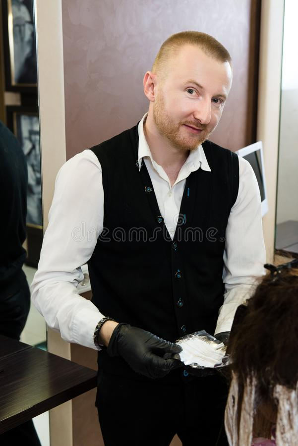 Man hairstylist posing for a picture while working with his client`s hair stock photos