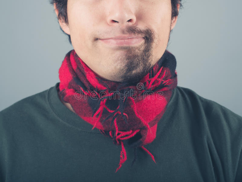 Man with half shaved beard wearing scarf. A young man with a half shaved beard is wearing a scarf royalty free stock photos