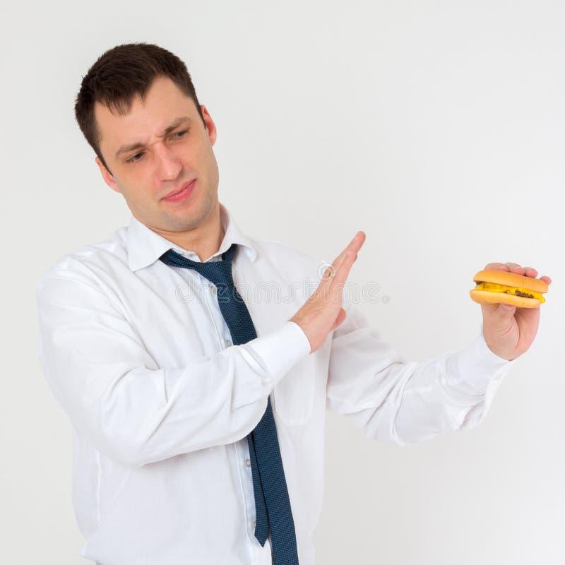 A man and a hamburger, no burger. The young man refuses a tasty burger stock images