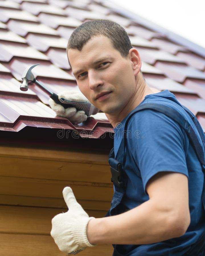 Man with a hammer in his hand mended the roof and shows that everything is fine royalty free stock photos