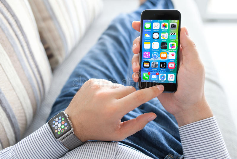 Man hand with Apple Watch holding iPhone stock photos