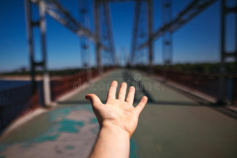 Man hand on background of steel bridge in city. summer travel co stock photo