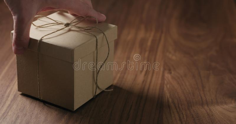 Man hand bring brown paper gift box on walnut table. Wide photo royalty free stock images