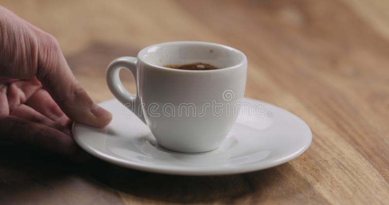 Man hand bring cup of fresh espresso on wood table. Wide photo stock photography