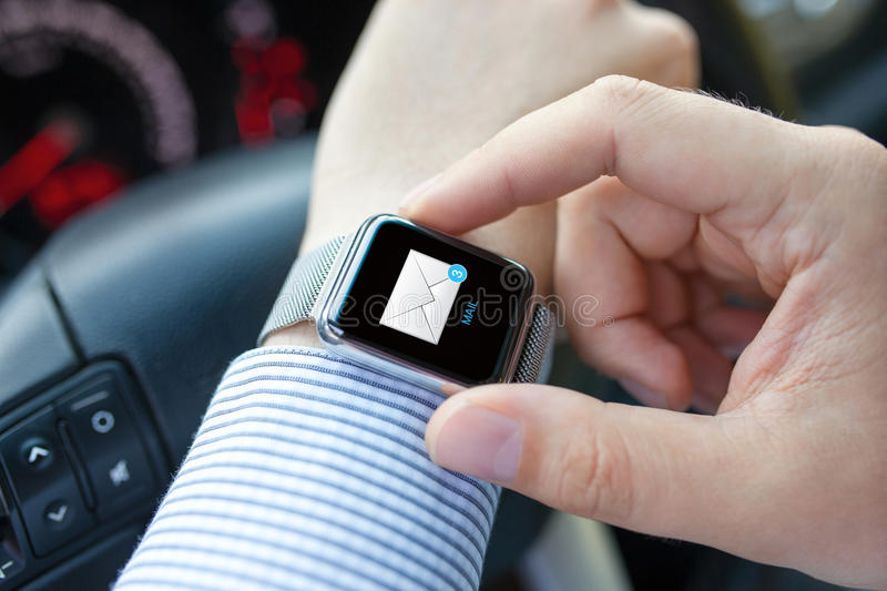 Man hand in car with watch and e-mail on screen stock photo
