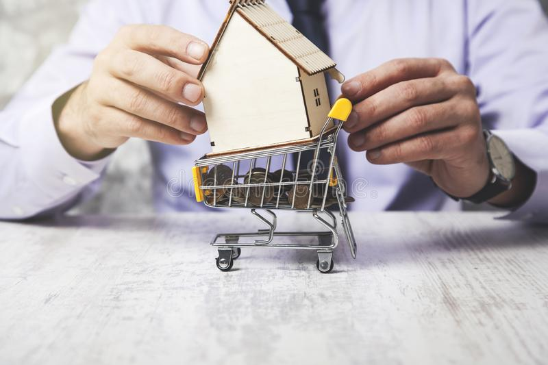 Man hand coins with house model. On basket royalty free stock images