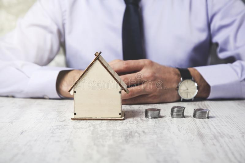 Man hand coins with house model. On the desk stock photography