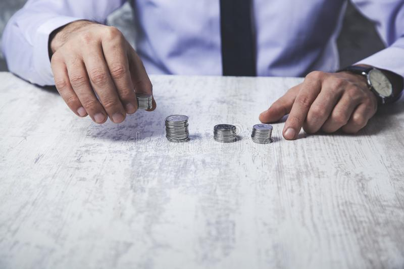 Man hand coins. Young business man hand coins on desk stock photography