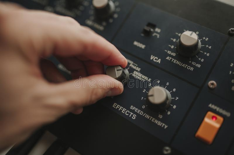 Man hand controlling musical keyboard buttons while playing music. royalty free stock image