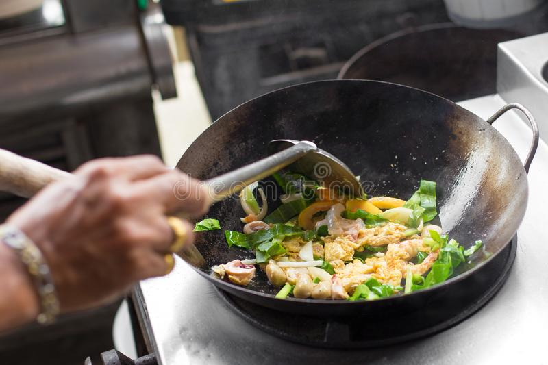 Man hand is cooking Asian style in a pan stock photos