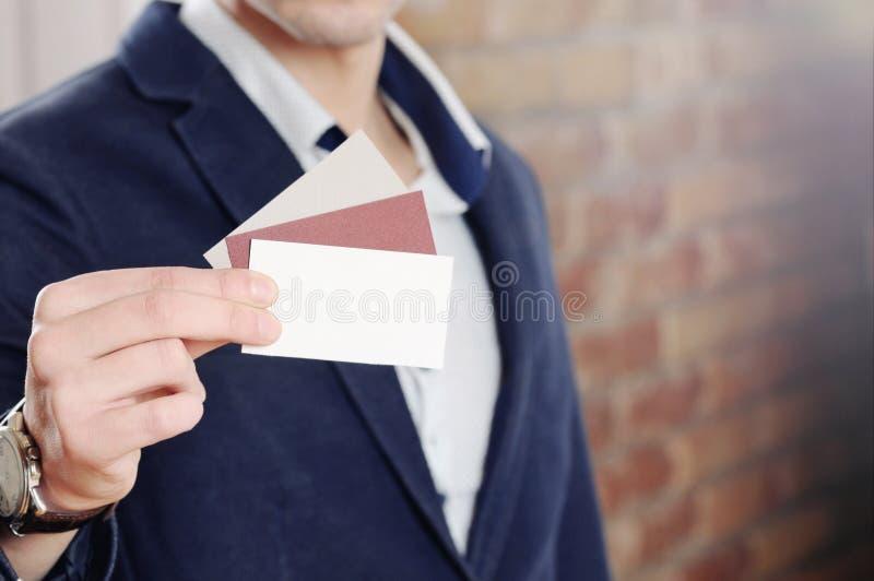 Man hand die adreskaartje tonen die - close-up op bakstenen muurachtergrond wordt geschoten stock foto