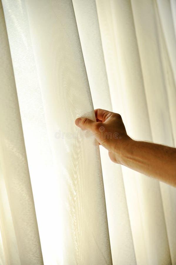 Man hand die een venstergordijn trekken royalty-vrije stock afbeelding
