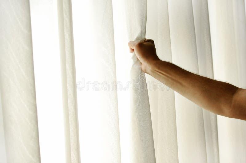 Man hand die een venstergordijn trekken stock foto's