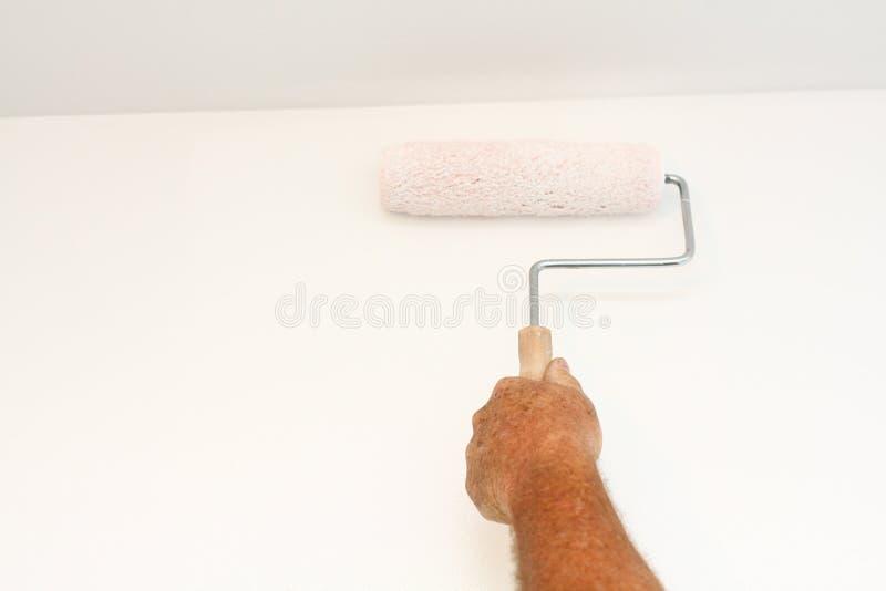Man hand die verfrol op witte muur met behulp van stock fotografie