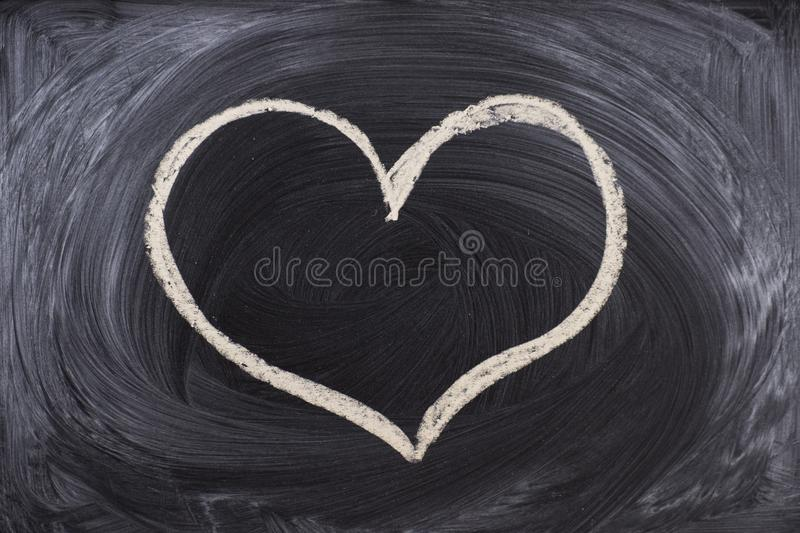 Man hand drawing a heart with chalk in a chalkboard stock photo