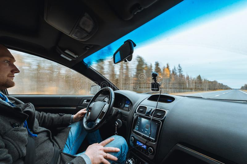 Man hand driving a car at Autumn Road between trees forest Male sit inside control volume audio system Empty copy space royalty free stock photos