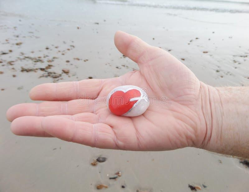 Man hand en een steen van de hartvorm - de St Valentine Dagliefde stock fotografie