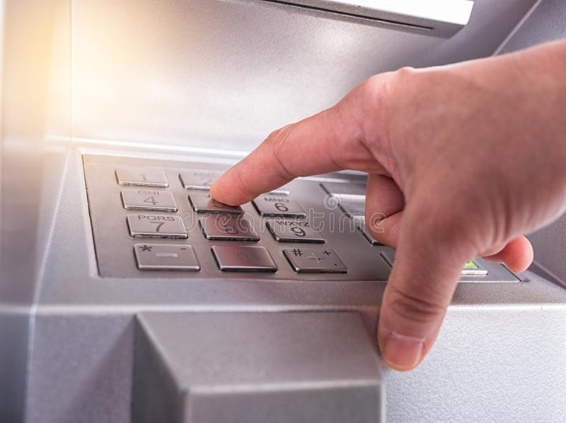Hand entering PIN pass code on bank machine keypad royalty free stock photos