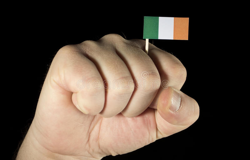 Man hand fist with Irish flag isolated on black. Background royalty free stock photography