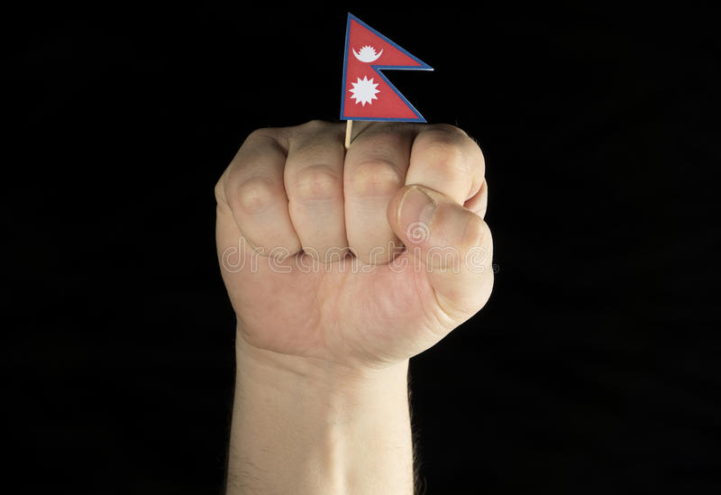 Man hand fist with Nepalese flag isolated on black. Background stock image