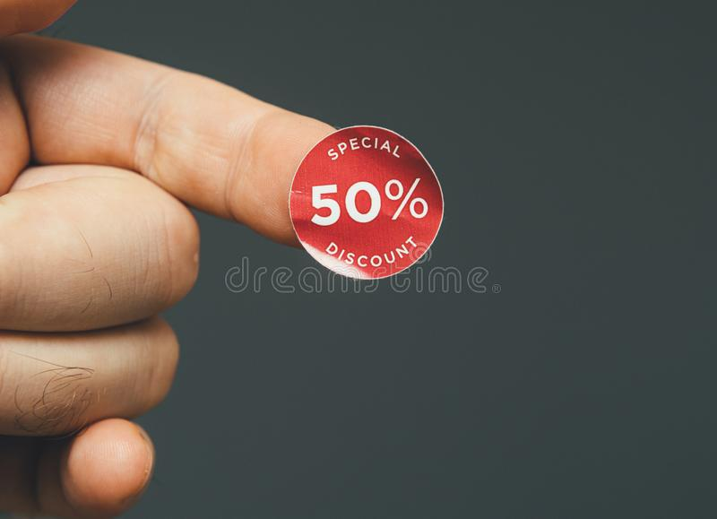 Man hand with glue sticked discount sale special price. 50 percent red tags to be glued on goods during sale season - isolated gray background stock image