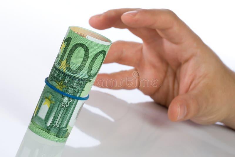 Grabbing a Roll of Money. Man hand grabbing a roll of Euro bills stock photo