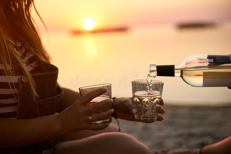 Man hand gracefully pouring white wine while girlfriend holding glasses. Couple enjoy beverage on sunset near sea stock photography