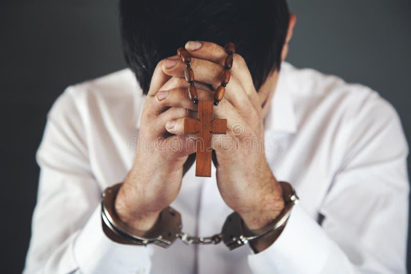 Man hand handcuffs with cross stock photo
