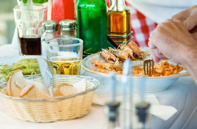 A man hand having lunch with shrimp, green pasta and beer outdoors in Mykonos stock photos