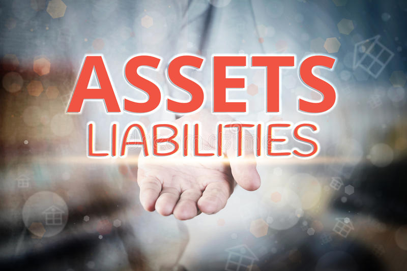 Man hand holding Assets Liabilities text on blurry home icon pro stock photo