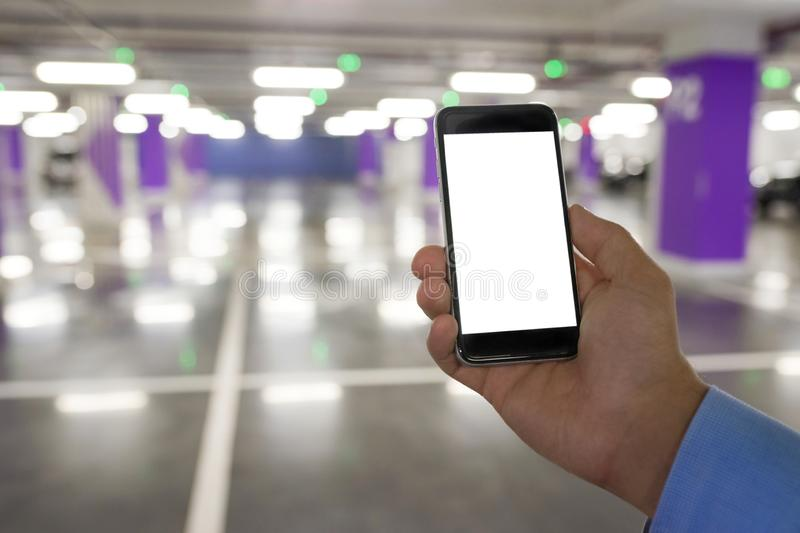 Man hand holding blank screen mobile phone for your text or content, in indoor car parking stock images