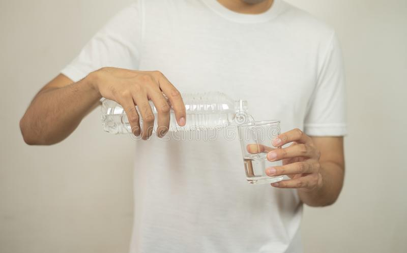 Man hand holding a bottle of water Pouring water into a glass stock photography