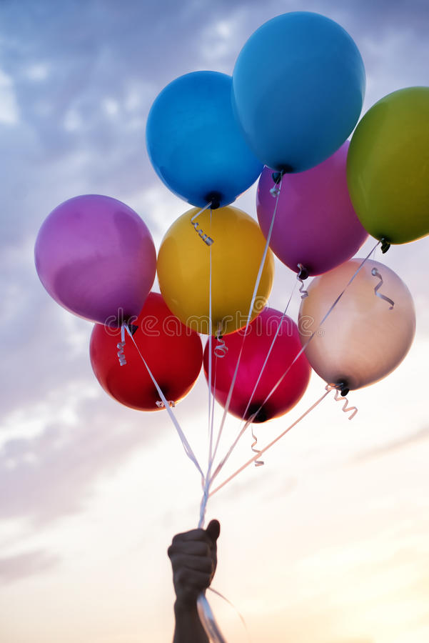 Man Hand Holding Colorful Balloons And A Beautiful Sunset. Birthday Party Balloons. Man Hand Holding Colorful Balloons And A Beautiful Sunset. Birthday Party royalty free stock photos