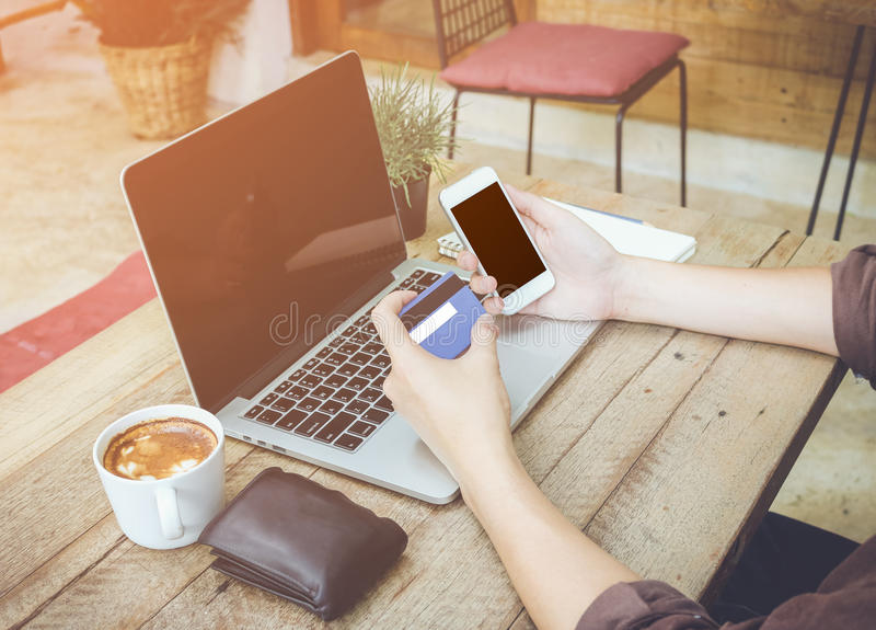 Man hand holding credit card use laptop and mobile phone vintage tone.  royalty free stock image