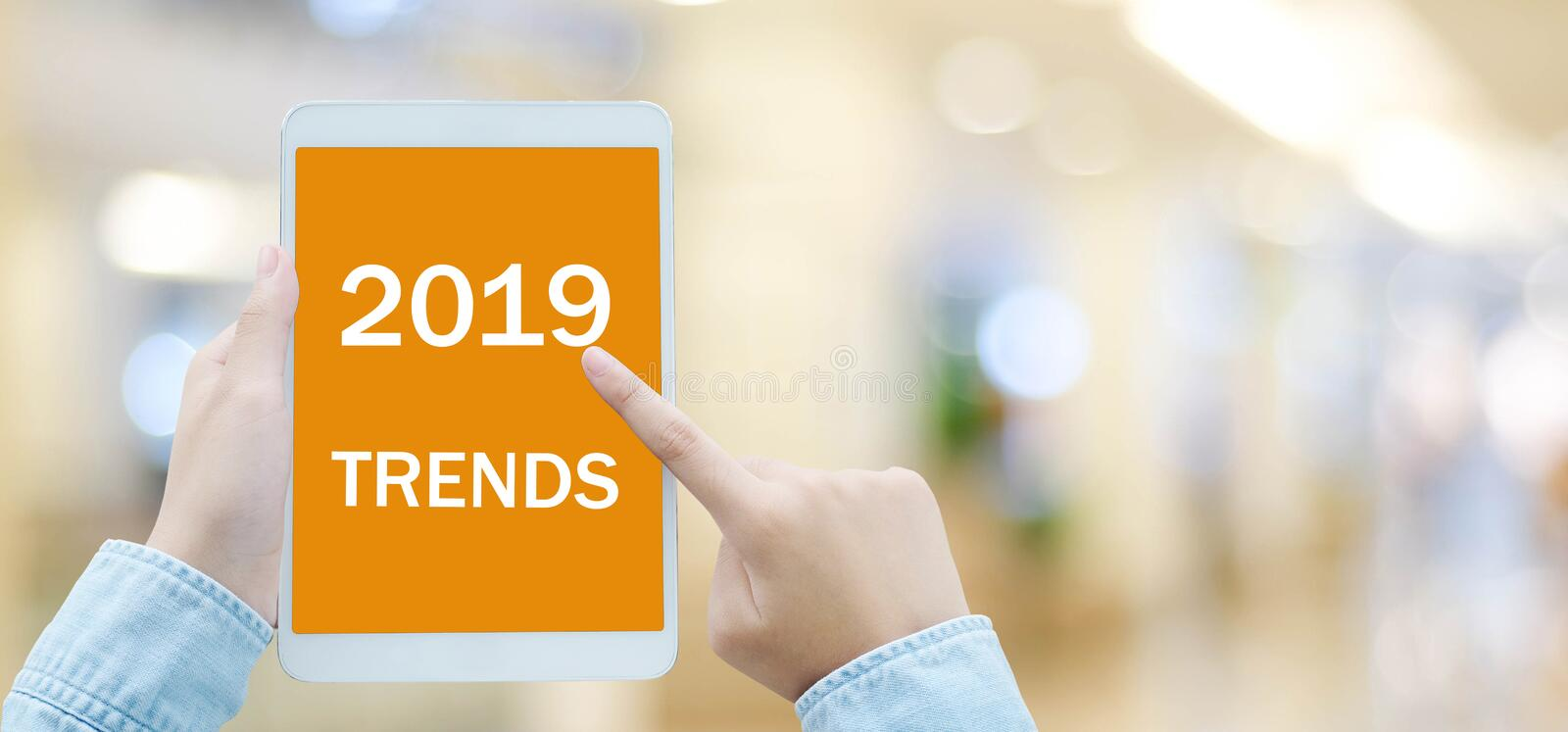 Man hand holding digital tablet with 2019 trends on screen background, digital marketing, business and technology concept. Man hand holding digital tablet with stock images