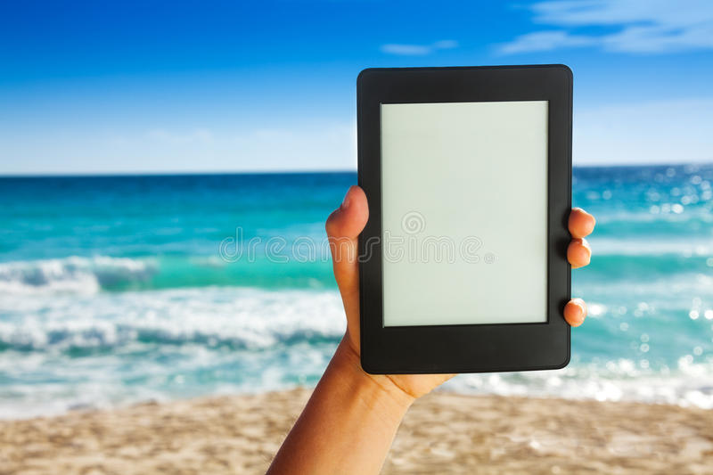 Man hand holding electronic device for reading. On white sand beach background stock images