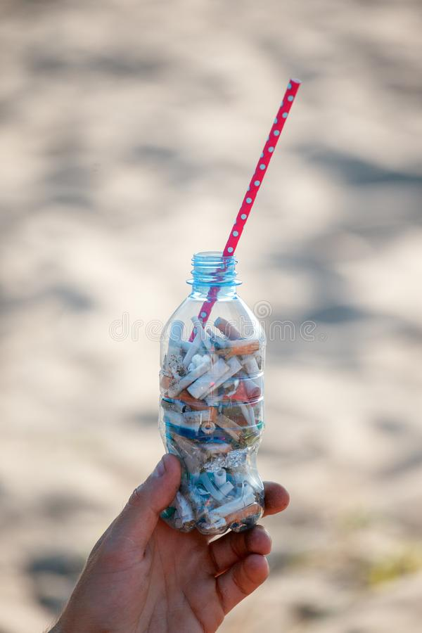Man hand holding Garbage on the beach trash, plastic, bottle, foam, rubbish. Ecological concept of pollution earth and world ocean royalty free stock photos