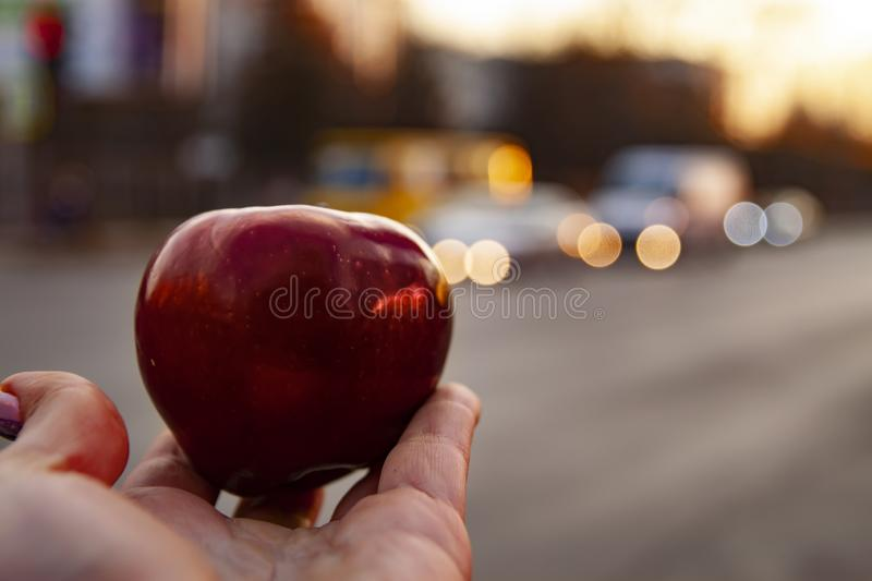 Man hand holding and giving big red apple on traffic cars background with copy space for text. Concept of proper diet. Fresh and stock photo