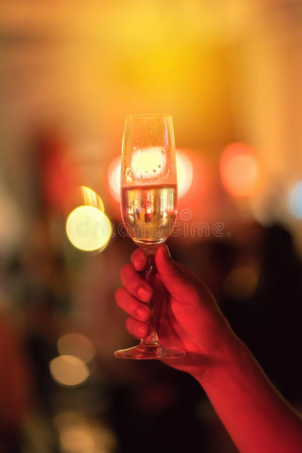 Man hand is holding a glass of white wine in night party royalty free stock photo