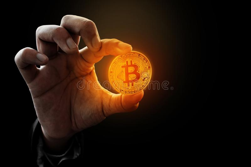 Man hand holding golden bitcoin. Man hand hold golden bitcoin royalty free stock photo
