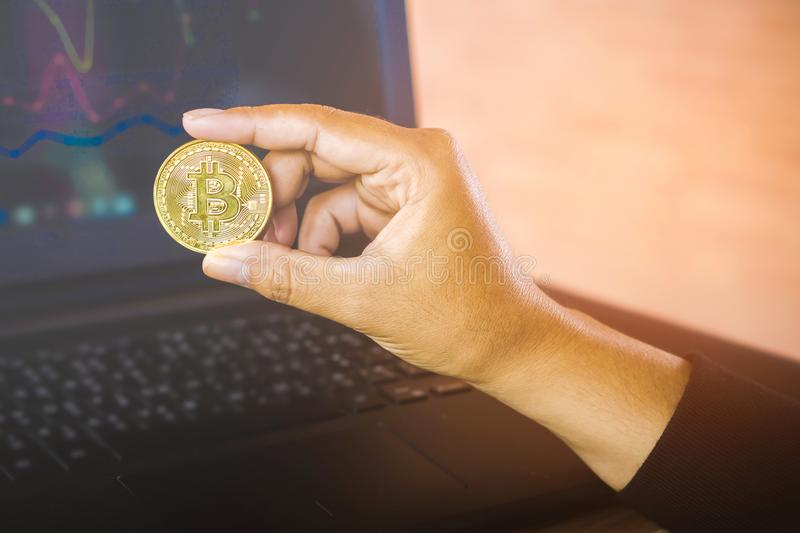 Man hand holding golden bitcoin over computer laptop in background with financial graph royalty free stock images