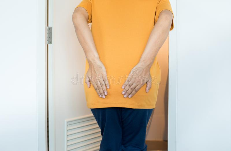 Men hands holding his bottom using toilet and suffers from Diarrhea and  Hemorrhoids after wake up in morning at home. Man hand holding his bottom using toilet royalty free stock image