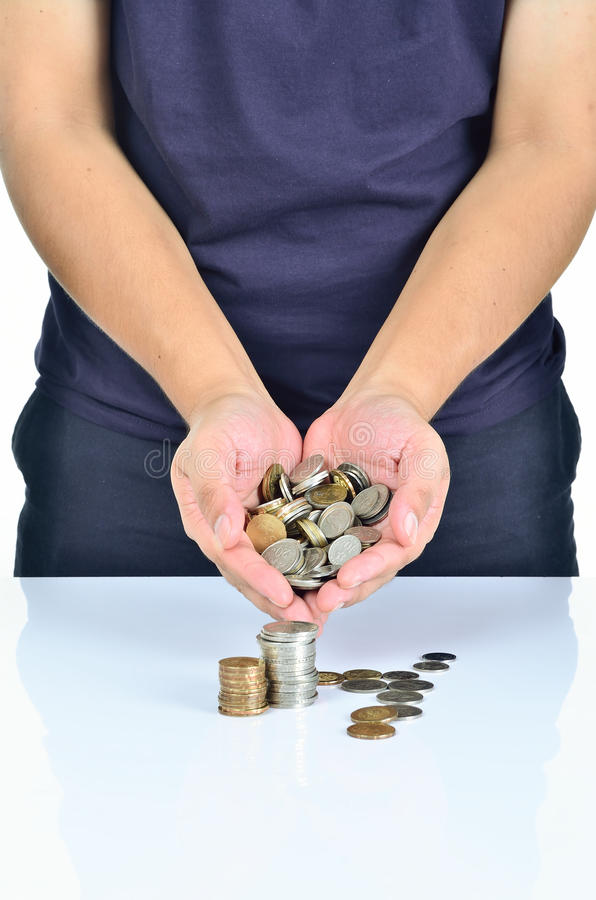 Man hand holding pile of coins stock photo