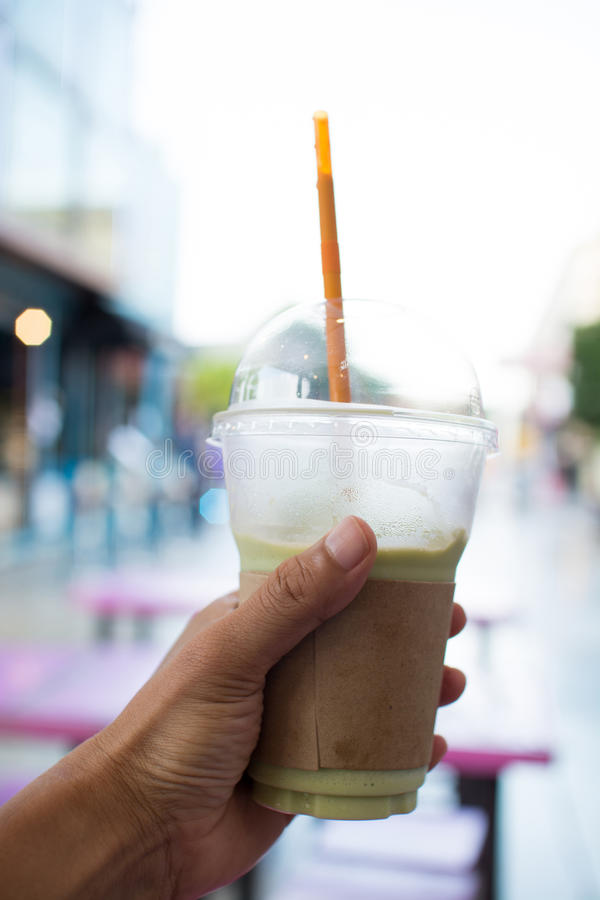 Man hand holding plastic glass of iced milk green tea royalty free stock photography