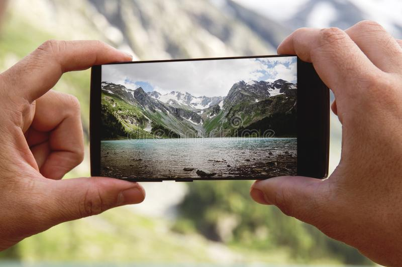 A man hand holding smart phone device in the mountains royalty free stock image