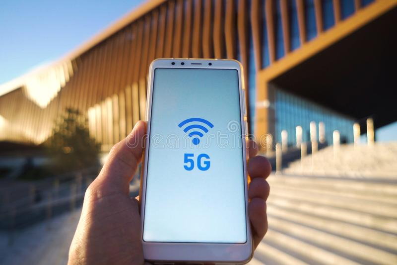 Man hand holding a smartphone and 5g signal symbol on screen with broadcast antenna icon on city background. High speed royalty free stock photography