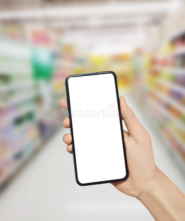 Man hand holding smartphone in Supermarket. Blurred background. Blank white screen for your text. stock image